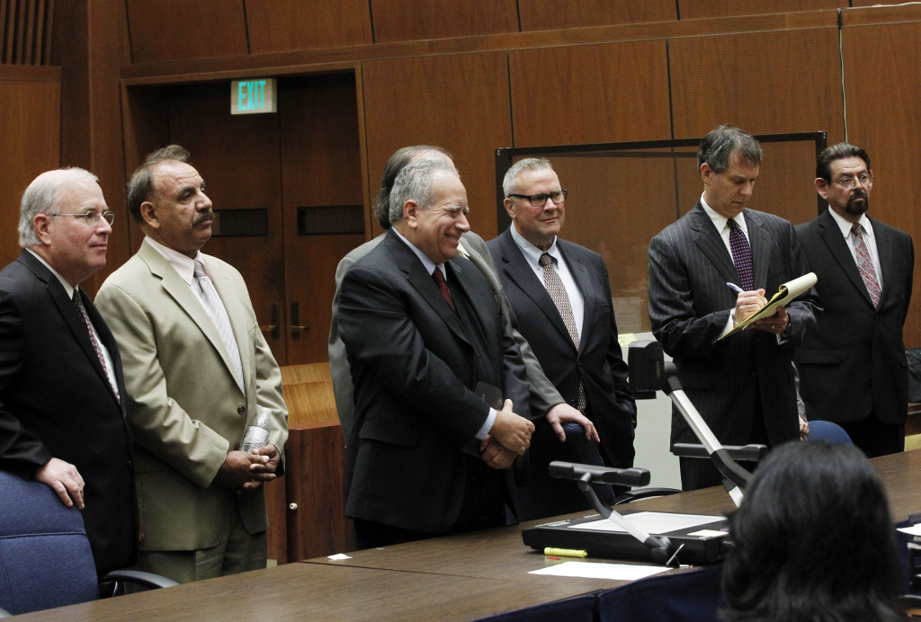 Second from left, former Bell Mayor Oscar Hernandez, fifth from left, George Cole, and far right, George Mirabal, defendants in the Bell corruption trial stand with their attorneys at a Los Angeles courthouse on Friday, Feb 21, 2014.