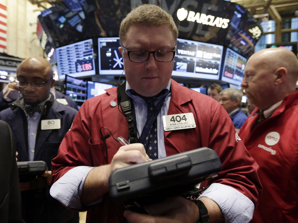 Trader Ryan Falvey (center), works on the floor of the New York Stock Exchange on Wednesday. Stocks were modestly higher in early trading on Wall Street Wednesday as the Federal Reserve ends its last two-day policy meeting of 2013.