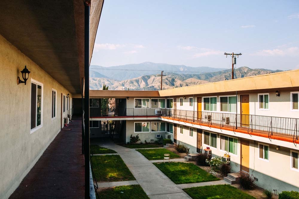 A courtyard at River Glen Apartments in San Bernardino, California, the peaks of the San Bernardino mountains loom in the distance.