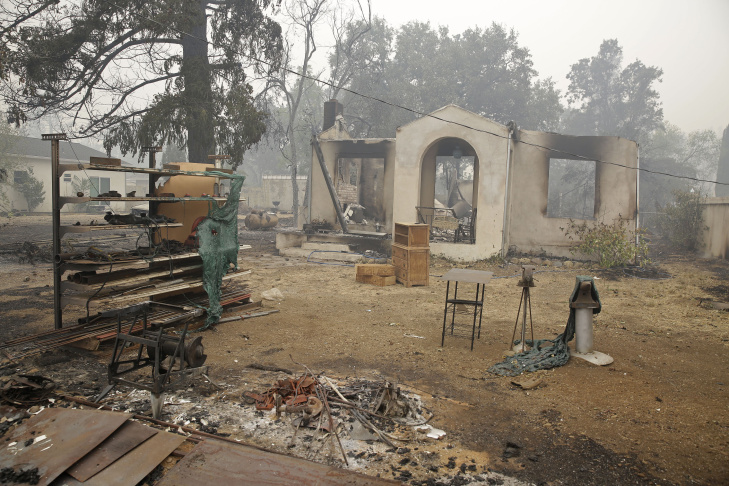 A frame and trees are all that is left around a home destroyed by fire Sunday, Sept. 13, 2015, in Middletown, Calif. California Gov. Jerry Brown has declared a state of emergency in Lake and Napa Counties after a wildfire charred more than 60 square miles within 12 hours, prompting thousands to flee their homes. Brown said Sunday the declaration will expedite debris removal and waive fees to people who need to replace official documents lost in the fire.  The blaze, about 100 miles north of San Francisco, has destroyed an unconfirmed number of homes and other buildings and damaged highways and other infrastructure.(AP Photo/Eric Risberg)