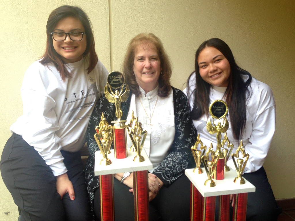 Stephanie Valdivia (Left) and Mercy Garcia (Right) of the winning team pose with their coach, Beatrice Rull after the Academic Bowl at the Autry National Center.