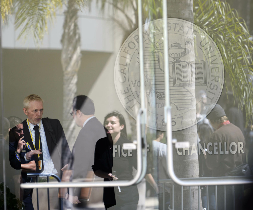 Demonstrators are reflected in windows at the main entrance to the CSU Chancellor's office in Long Beach Wednesday. Students and activists were showing their opposition to a systemwide $280 per semester