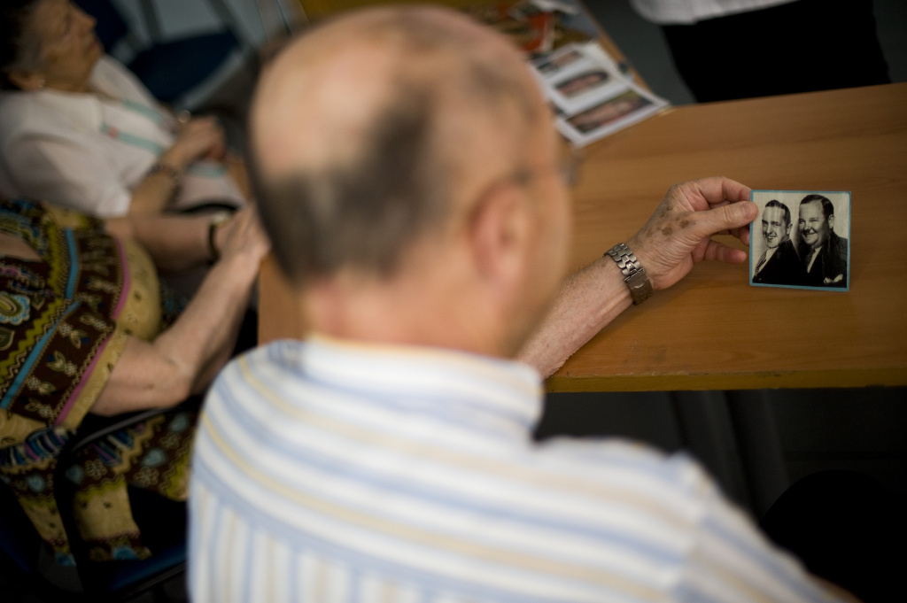 A man holds a photo during a memory activity at an elderly home specializing in Alzheimer's disease.