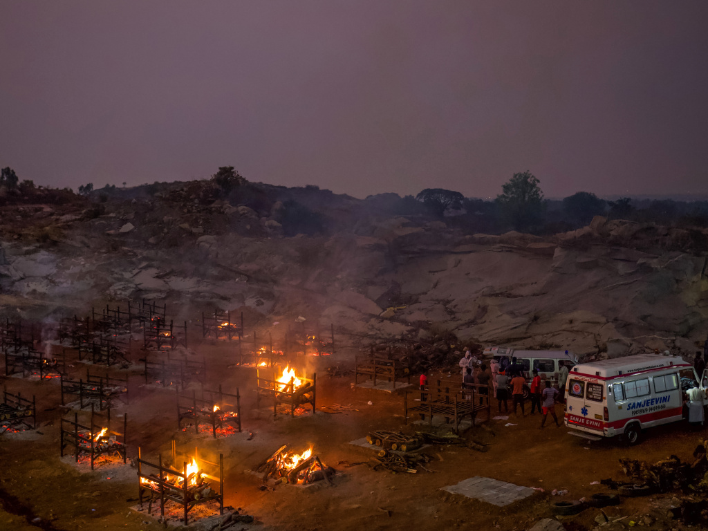 Funeral pyres burn in a disused granite quarry repurposed to cremate the dead due to COVID-19 on Friday in Bengaluru, India. The U.S. is set to impose new travel restrictions against travelers from the country.