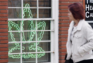 A pedestrian walks past a marijuana leaf neon sign advertising a medical marijuana provider along a street in the Sherman Oaks section of Los Angeles, Calif. on Tuesday Jan. 26, 2010. Tuesday the LA City Council approved an ordinance that will close hundreds of clinics while those that remain said they would be banished to industrial areas forcing their clients to travel longer distances.