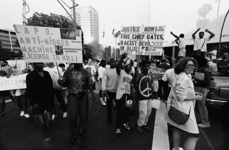 File: A group of people hold up signs advocating changes in the Los Angeles Police Department during the LA Riots unrest on April 29, 1992.
