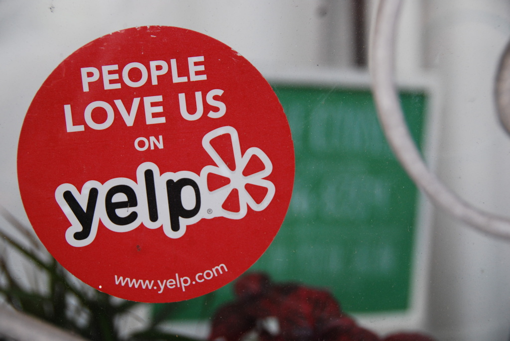 A Yelp sticker on the window of a business.