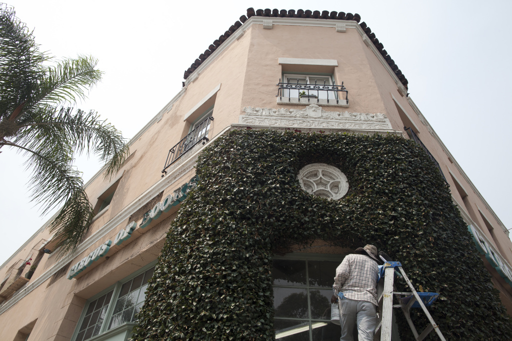 A man cleans the windows on the outside Wendell Jones' apartment in West Hollywood where he fought to keep his rent-controlled apartment.