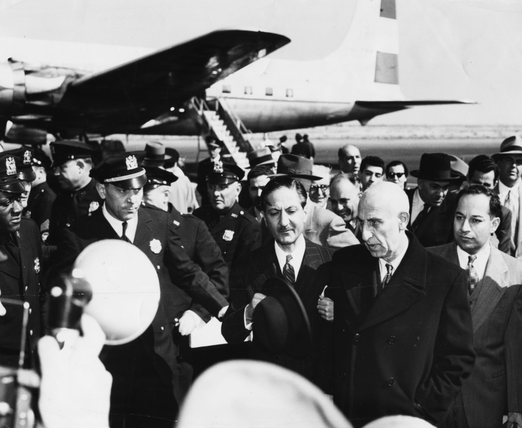 Iranian politician Mohammed Mossadegh, surrounded by press and officials as he arrives at an airport, circa 1955.