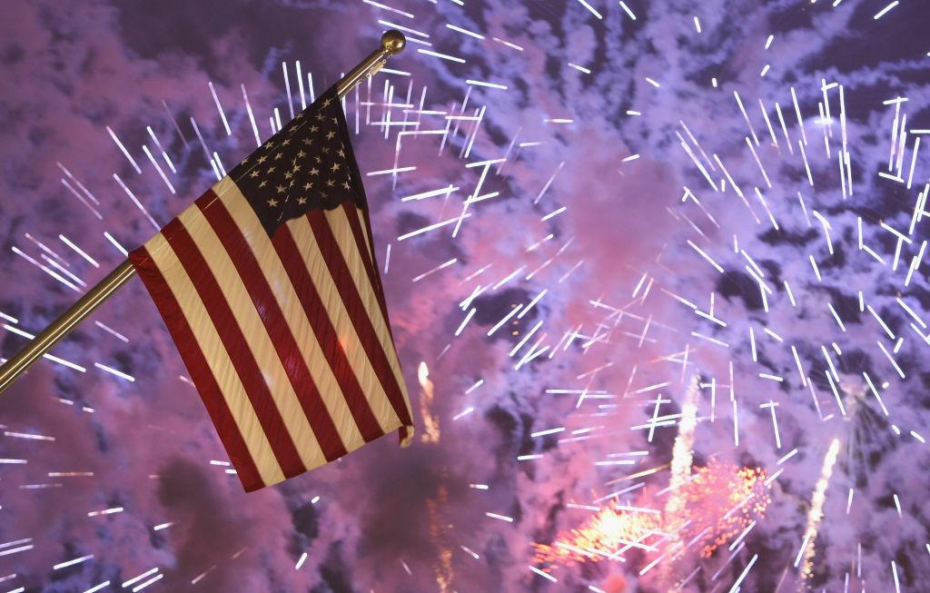 Fireworks explode behind the U.S. flag.