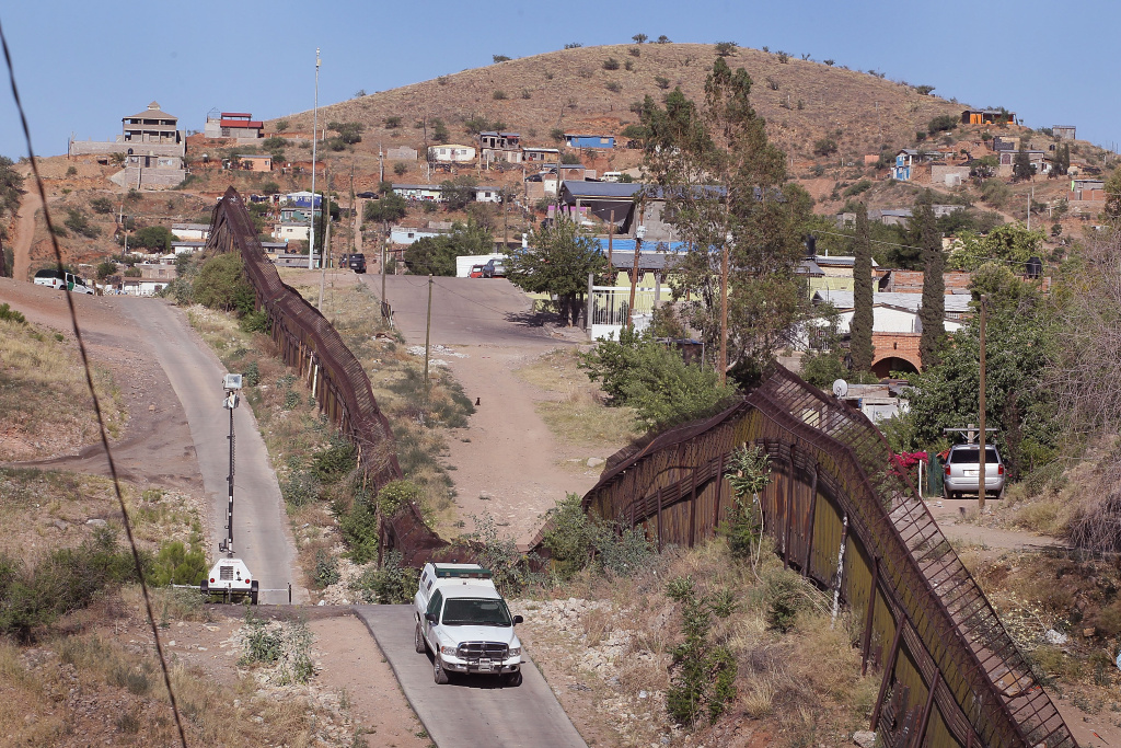 A U.S. Customs and Border Protection agent drives along the border fence which separates the cities of Nogales, Arizona and Nogales, Sonora Mexico. Some border residents have mixed views on illegal immigration.