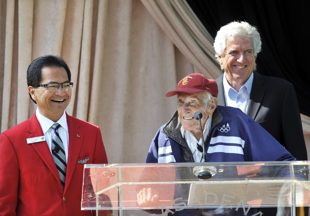 American war hero and Olympian Louis Zamperini (center) was chosen as the Grand Marshal for the 2015 Tournament of Roses in May of 2014. Zamperini speaks here with his son Luke Zamperini (R) and Tournament of Roses President Richard L. Chinen (L).