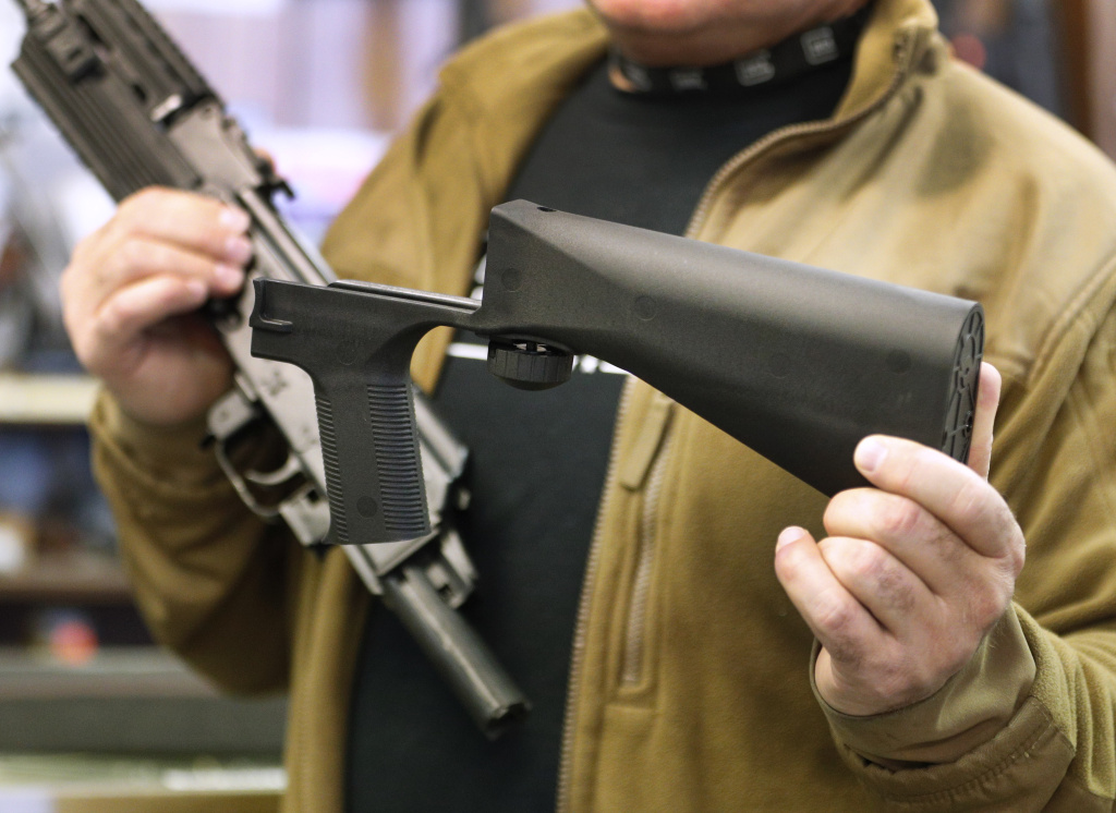 A bump stock device (right), that fits on a semi-automatic rifle to increase the firing speed, making it similar to a fully automatic rifle, is shown next to a AK-47 semi-automatic rifle (left) at a gun store on October 5, 2017 in Salt Lake City, Utah.