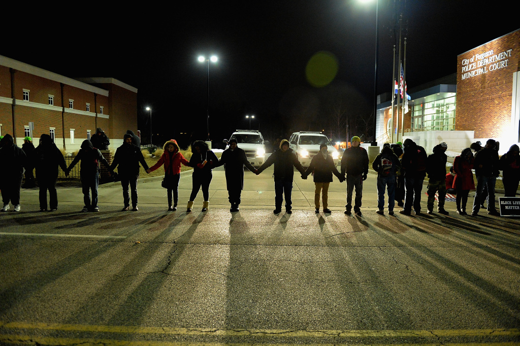 FERGUSON, MO -  MARCH 4: Protestors demonstrate outside the Ferguson Police Department in Ferguson, Missouri on March 4, 2015. The Federal Department of Justice decided today not to charge then Ferguson Police Officer, Darren Wilson, of any wrongdoing in the August shooting of Michael Brown Jr. The Department of Justice investigation did happen to find Ferguson Police Departments involvement in racially based policing. (Photo by Michael Thomas/Getty Images)