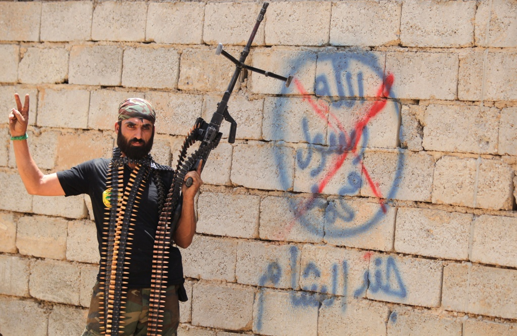 A heavily armed Iraqi Shiite fighter from the Popular Mobilisation units flashes the V for victory sign in front of graffiti of the Islamic State (IS) group in the town of Baiji, north of Tikrit, as allied Iraqi forces fight against the jihadist group to try to retake the strategic town for a second time, on June 9, 2015.
