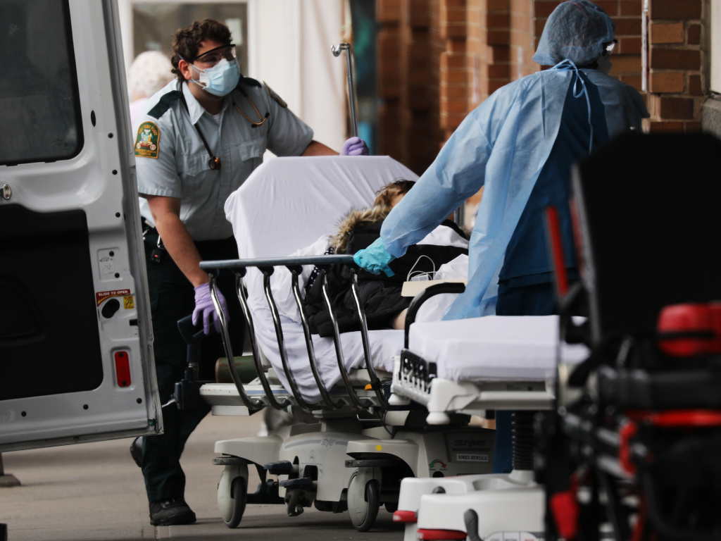A patient with suspected COVID-19 arrives at Maimonides Medical Center in Brooklyn Thursday. Even as the risk of big medical bills climbs, many Americans are losing their jobs and health insurance right now.