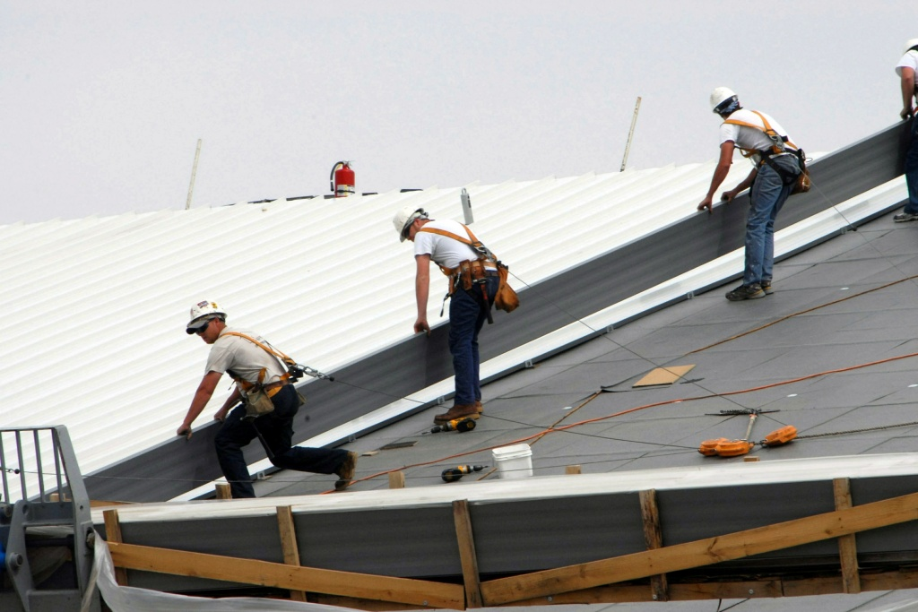 Workers install a cool roof at the National Nuclear Security Administration in Washington, D.C. in 2009. Usually white or light colored, they can be up to 55 degrees cooler than regular roofs.