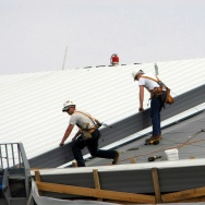 Workers install a cool roof. Usually white or light colored, they can be up to 55 degrees cooler than regular roofs.