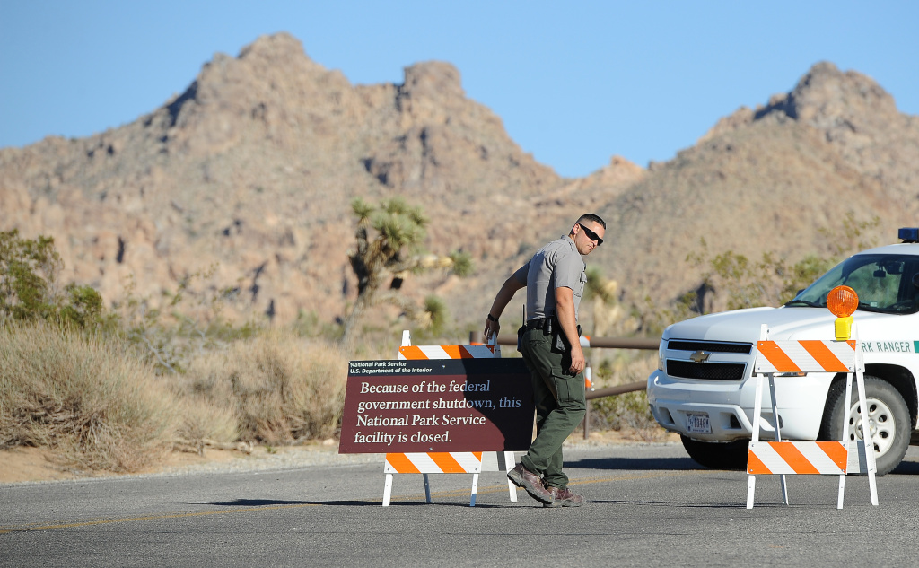 An US Park Ranger sets up a sign announcing the closure of Joshua Tree National Park, in Joshua Tree, California on October 2, 2013, the second day of the US government shutdown. Hundreds of tourists staying in landmark US national parks like Yosemite and the Grand Canyon face a deadline October 3, 2013 to leave due to the government shutdown.