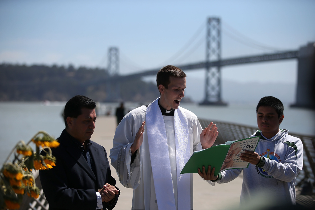Father Cameron Faller (C), associate pastor at the Church of the Epiphany, conducts a prayer service at the site where 32-year-old Kathryn Steinle was killed on July 6, 2015 in San Francisco, California. According to police, Steinle was shot and killed by Francisco Sanchez as she walked with her father on San Francisco's Pier 14 on July 1. Sanchez had been previously deported five times.