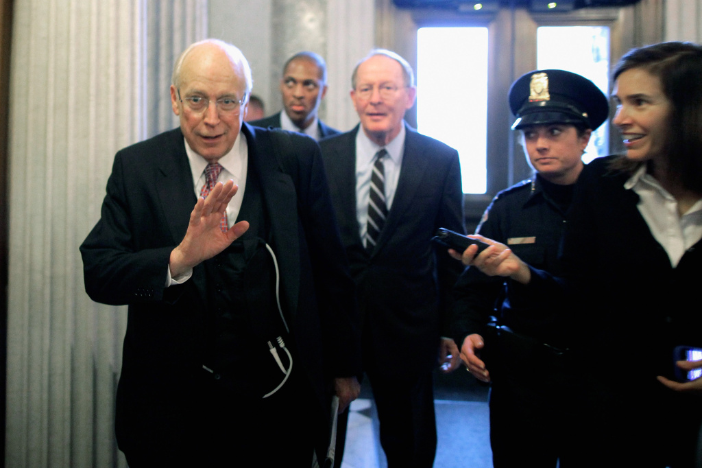 Former U.S. Vice President Dick Cheney (L) refuses to answer press questions as he leaves the Senate Republican policy luncheon with Sen. Lamar Alexander (R-TN) (3rd L) at the U.S. Captiol November 29, 2011 in Washington, DC.
