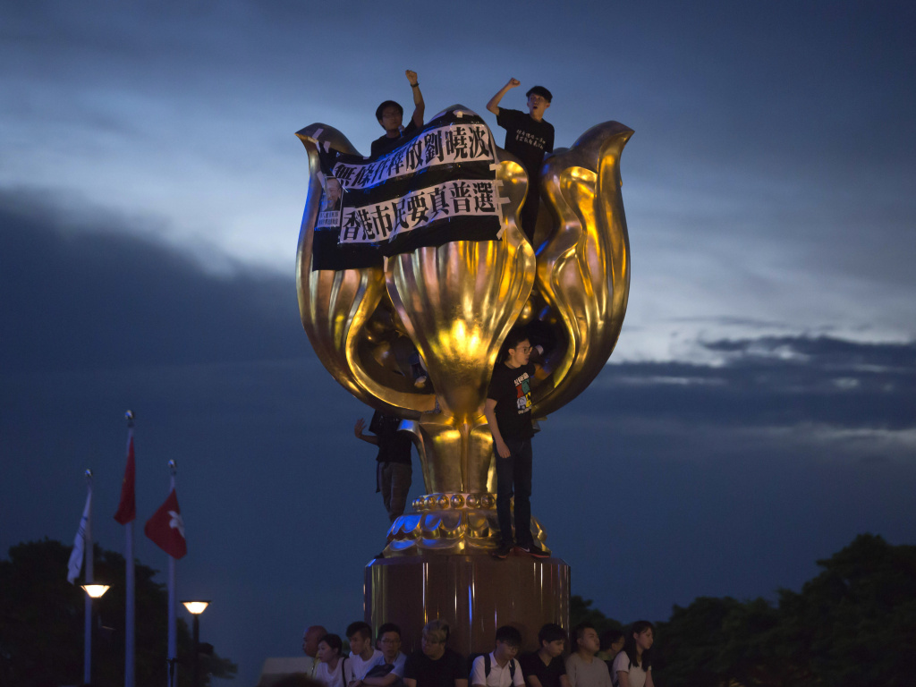 Pro-democracy activists hang a black cloth with a message demanding universal suffrage and the release of jailed Chinese Nobel Peace laureate Liu Xiaobo on the Golden Bauhinia flower statue in Hong Kong. On Monday, they had obscured the statue — a gift from Beijing to Hong Kong — with black cloth.