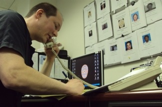 Actor and volunteer detective James Elliott makes calls in front of a board with pictures of missing people.