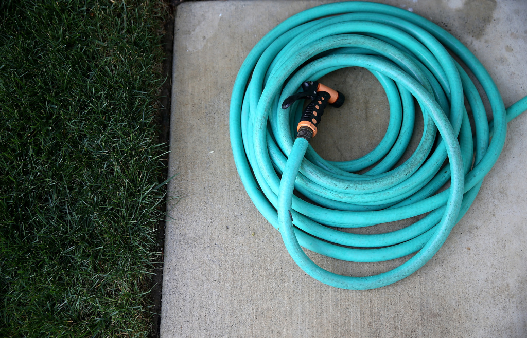 A coiled up hose sits next to a lawn on April 7, 2015 in Walnut Creek, California, just days after Governor Brown called for the first ever mandatory water conservation rules in the state.