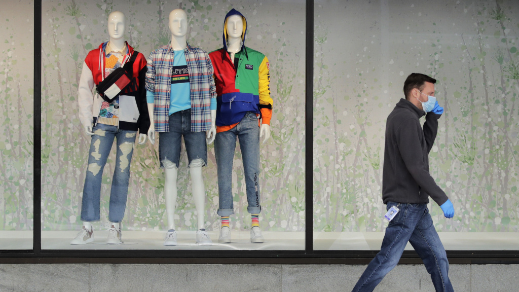 A man walks past mannequins in the windows of a Macy's store in Boston on April 15. The company said its online sales started growing in April, but they