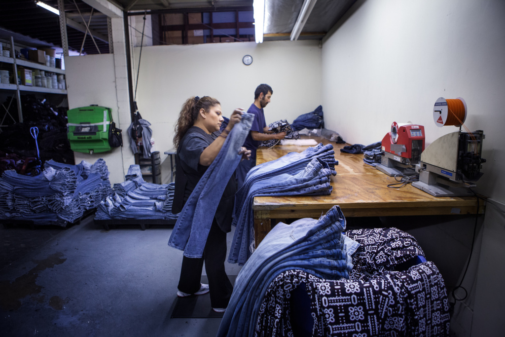 The Labor Department Tuesday said Americans' wages increased at a faster rate from January through March than the previous quarter, a trend that helped boost economic growth. But their benefits barely grew. (Photo: Workers inspect designer jeans at a factory in Lynnwood, Calif.)
