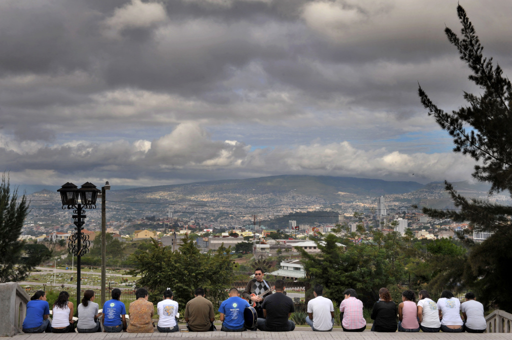 A group of youths studies the Bible, at the steps of the Suyapa Virgin basilica, in Tegucigalpa, Honduras, on October 3, 2009.