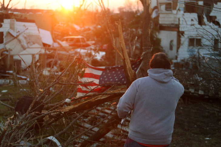 A person stands amongst damaged buildings along Washington Road in the aftermath of a tornado on November 18, 2013 in Washington, Illinois. A fast-moving storm system that produced several tornadoes that touched down across the Midwest left behind a path of destruction in 12 states.