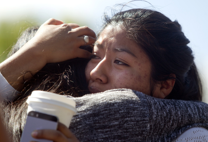 A Reynolds High School student is reunited with her parents after a shooting at her school June 10, 2014 in Troutdale, Oregon. Authorities said one student was fatally shot and the gunman was found dead at an Oregon high school.