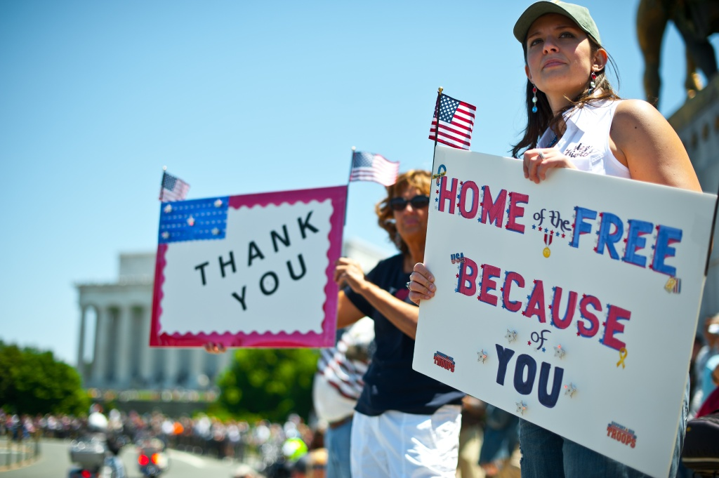 Two women hold up signs thanking the troops as members of the US military veterans' Rolling Thunder bikers group ride past in Washington on May 26, 2013 as the country marks Memorial Day.