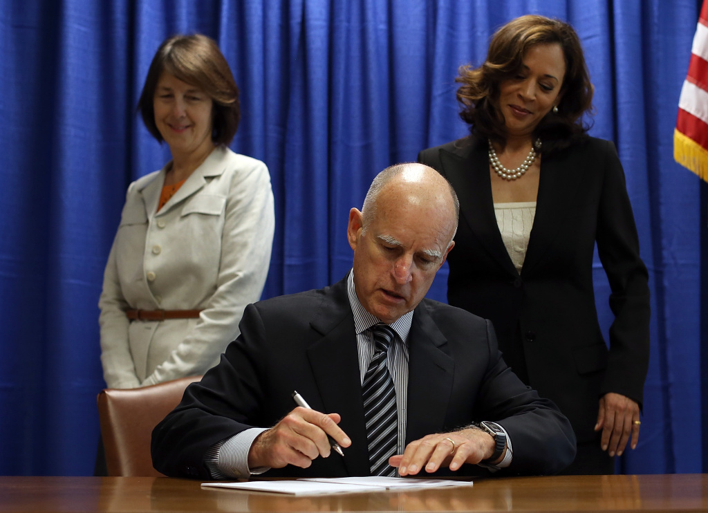 California Governor Jerry Brown (C) signs copies of the California Homeowner Bill of Rights (AB 278 and SB 900).
