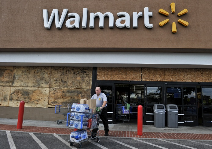 A man walks out of a boarded up Walmart