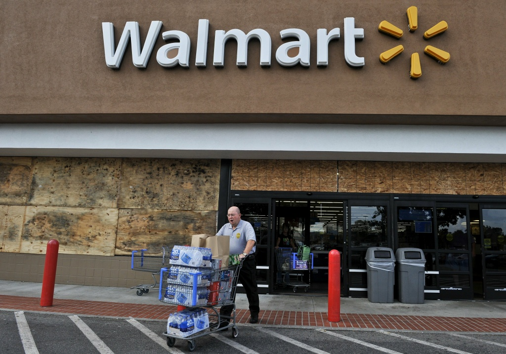 A man walks out of a boarded up Walmart store with a cart full of bottled water and other supplies in Kitty Hawk in the North Carolina Outerbanks on August 26, 2011 ahead of the expected landfall in the area of Hurricane Irene. Millions of people on the US east coast braced for the hurricane, a massive storm officials fear will cause widespread flooding and dangerous conditions up the seaboard. Officials from North Carolina to New York declared states of emergency as tens of thousands of the most vulnerable residents were ordered to higher ground as Irene raced toward the US mainland.    AFP PHOTO/Nicholas KAMM (Photo credit should read NICHOLAS KAMM/AFP/Getty Images)
