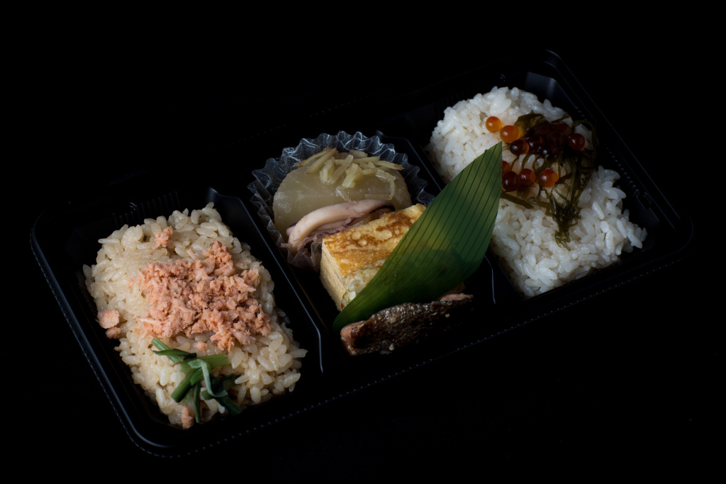 A bento box containing salmon over rice and salmon roe over rice from a convenience store or
