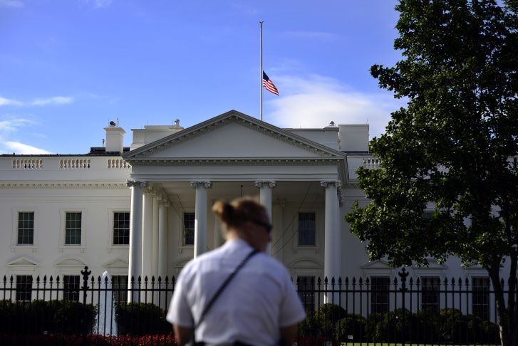 A member of the US Secret Service Uniform Division guards as the national flag flies half-mast on the roof of the White House on September 17, 2013 a day after deadly Navy Yard shooting in Washington, DC. Investigators on Tuesday tried to piece together what led a former US Navy reservist to open fire at a Washington base, killing 12 people before being gunned down by police. Police identified the gunman as Aaron Alexis of Fort Worth, Texas, who served in the Navy from 2007 to 2011 before becoming a defense subcontractor for computer giant Hewlett-Packard.