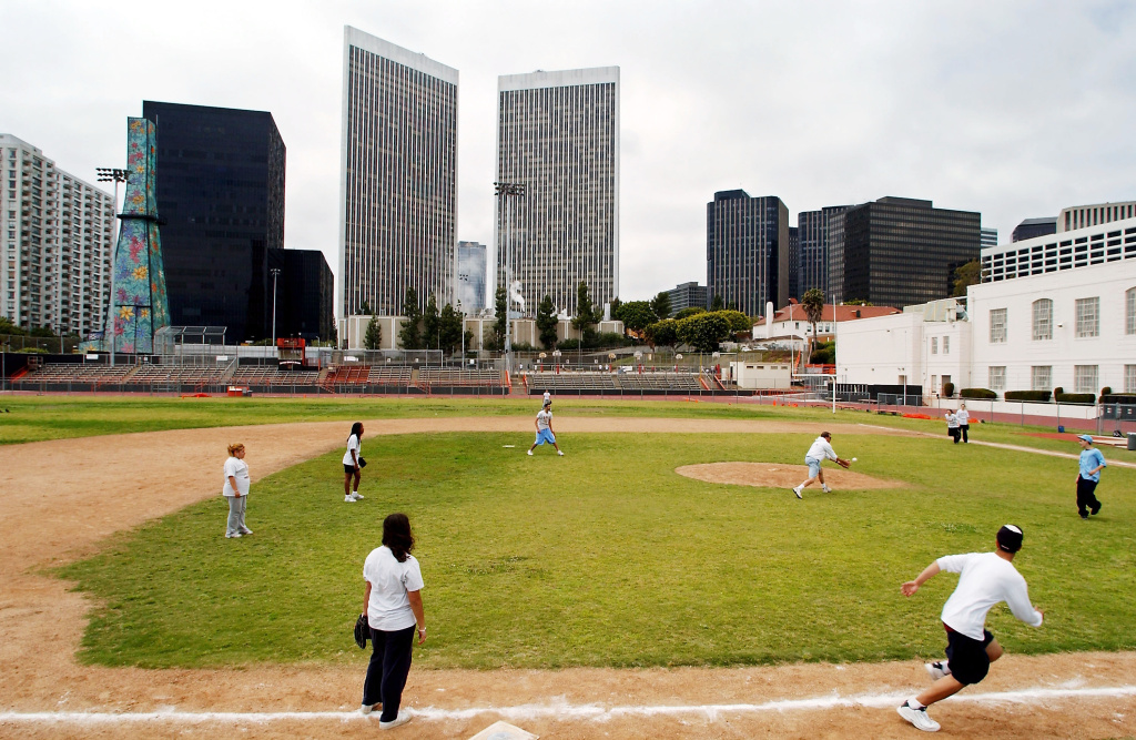 Students at Beverly Hills High School play softball within sight of an oil well tower (L) covered in flower designs May 7, 2003 in Beverly Hills, California.