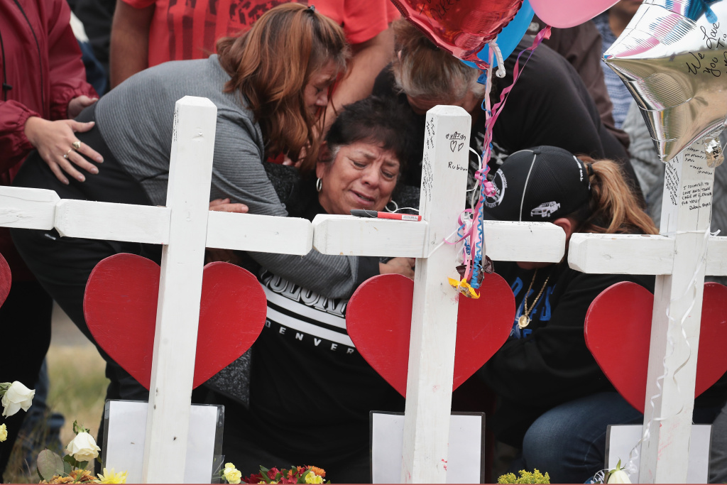 Lilly Navejan is comforted after breaking down while visiting a memorial to honor the 26 people killed at the First Baptist Church of Sutherland Springs on November 5, 2017 in Sutherland Springs, Texas. Navejan lost her brother, Ricardo Rodriguez, and his wife, Therese, in the mass shooting.