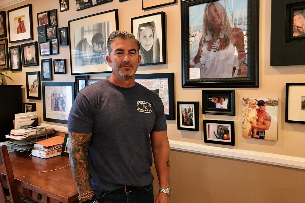 Paul Wilson stands next to a photo of his late wife, Christy Wilson (in white) on Aug. 17, 2017. Christy Wilson was one of eight victims of a 2011 shooting at a beauty salon in Seal Beach. An Orange County judge will decide on Aug. 18 whether the state can pursue the death penalty against confessed shooter Scott Dekraai.
