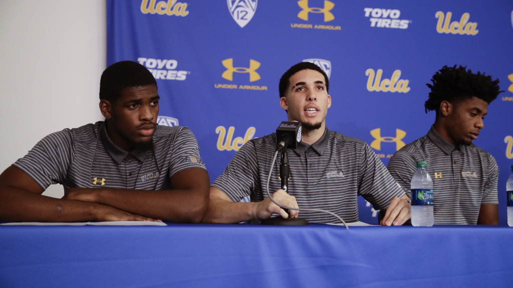 Flanked by teammates Cody Riley (left) and Jalen Hill, UCLA basketball player LiAngelo Ball reads his statement during a news conference at UCLA on Wednesday.
