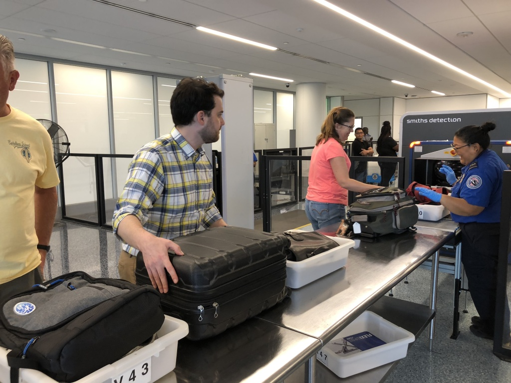Passengers prepare their carry-on luggage for the new 3D scanner.