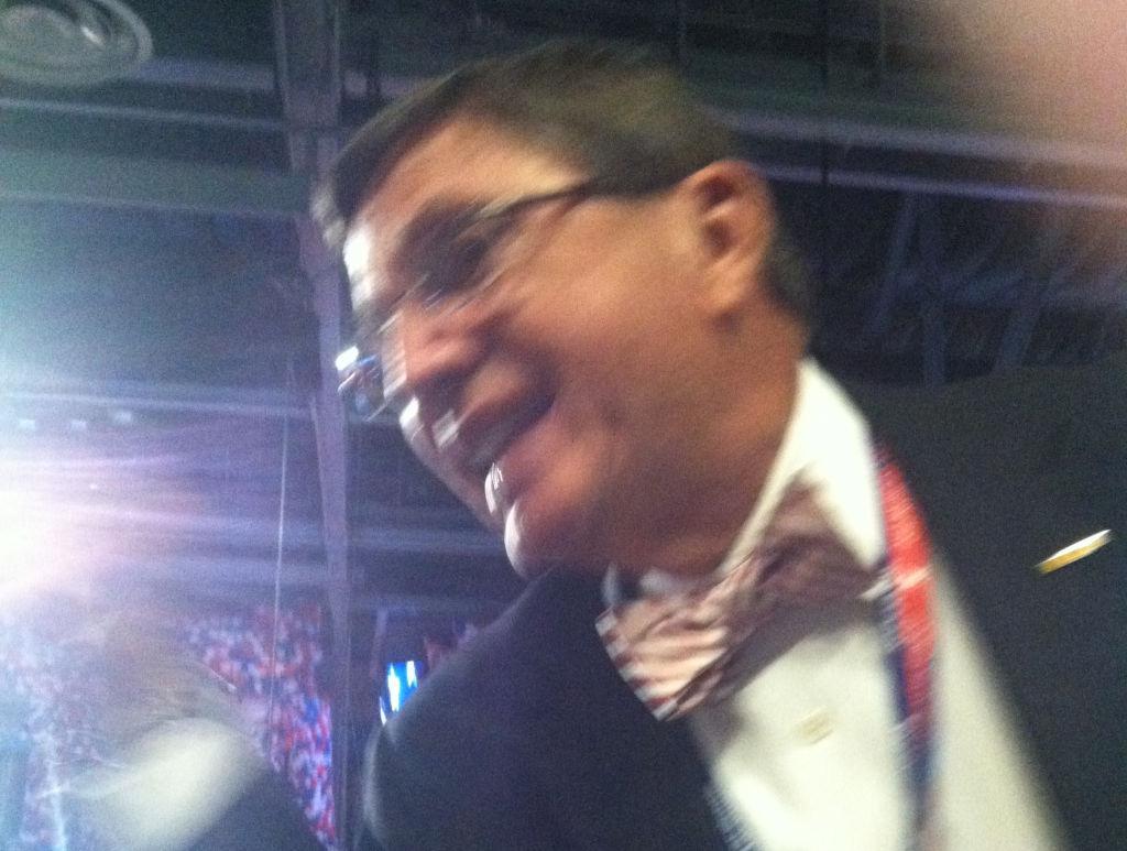 A man shouts back at a heckler sitting next to AirTalk producer Lauren Osen at the 2012 Republican National Convention.