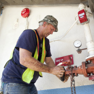 Dan Sapia shuts off water to the fire sprinklers at Hoover Street Elementary School in the Los Angeles Unified school district. His plumbing crew is often pulled from one emergency job, such as repairing this water main leak, to another, leaving little time for outstanding requests.