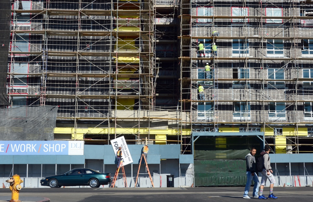 Pedestrians cross the street as construction workers work on the exterior of a commercial and residential building going up in Hollywood, California on January 22, 2014.