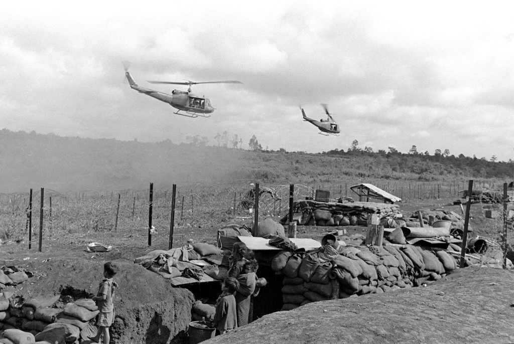 File: Vietnamese civilians to be evacuated watch helicopters arriving at an American camp in Plei Me, south Vietnam, Nov. 1, 1965.