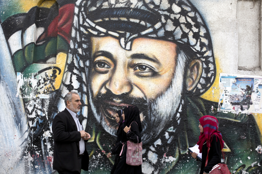 Palestinians walk past a mural of late Palestinian leader Yasser Arafat in Gaza City on November 7, 2013. Swiss scientists have concluded that Arafat probably died from polonium poisoning, according to a text of their findings published by Al-Jazeera television on November 6.