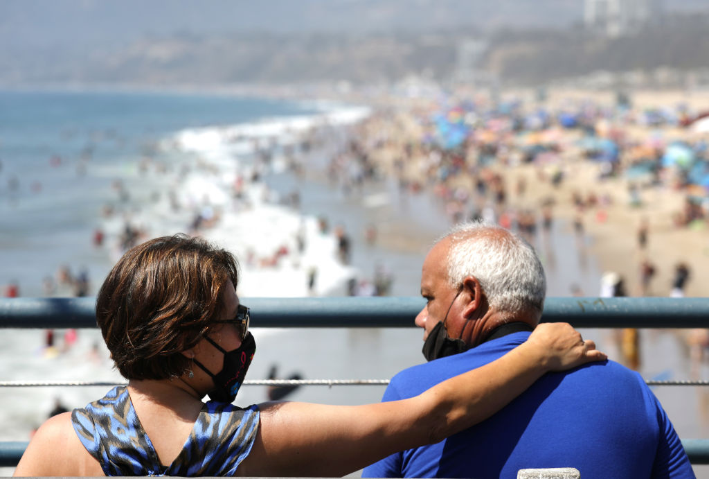 People sit on the Santa Monica pier as others gather on the beach at the Pacific Ocean on the first day of the Labor Day weekend amid a heatwave on September 5, 2020 in Santa Monica, California.
